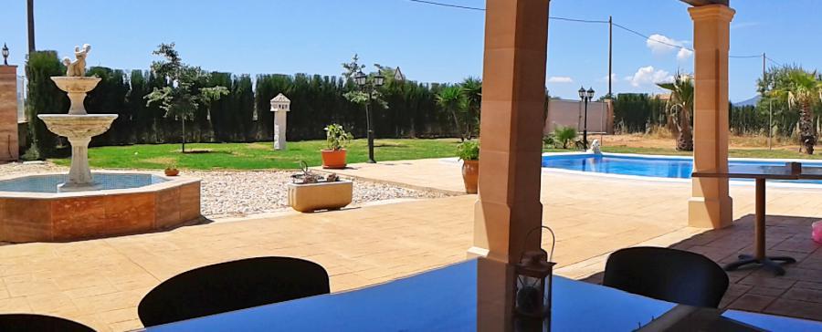 Überdachte Terrasse mit Blick zum Pool und Garten