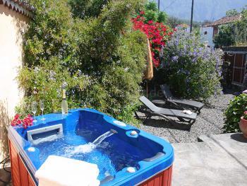 Kleiner Garten mit Jacuzzi und Sonnenliegen