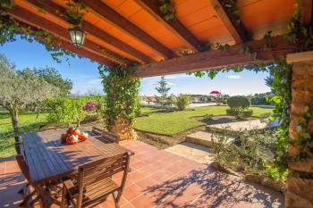 Grillterrasse mit Blick zum Pool und Garten